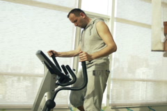 Man exercising on elliptical machine in gym, super slow motion, 240fps NTSC Stock Footage