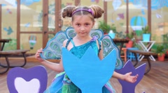 Little girl in fairy costume depict bird in children cafe Stock Footage