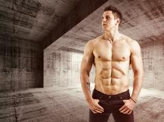 Muscular shirtless young man with jeans, indoors in empty warehouse Stock Photos