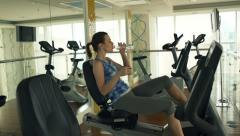 Woman drinking water on stationary bike in gym, super slow motion, 240fps HD Stock Footage