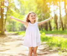 Positive charming curly little girl enjoying summer sunny day, expression emo Stock Photos