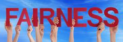Hands Holding Red Straight Word Fairness Blue Sky - stock photo