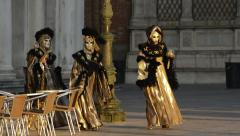 Three carnival dressed actors in St Mark's Square at sunrise in Venice Italy Stock Footage
