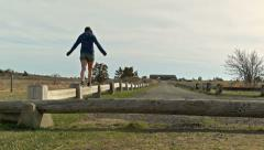 Teenager balances on a wooden guardrail Stock Footage