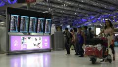 People near information board in Bangkok international airport, Thailand Stock Footage