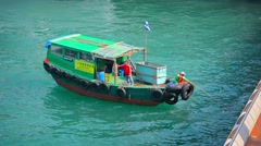 HONG KONG, CHINA - CIRCA JAN 2015: Workers on a small utility boat skim trash - stock footage