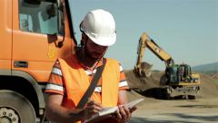 Construction manager writing in notebook,in blurred background excavator.Worker. Stock Footage