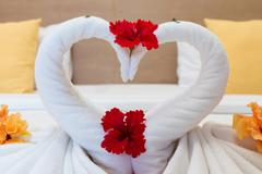 White swans made from towels on bed in the hotel Stock Photos