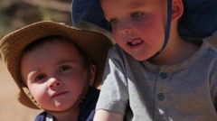 Little boys climing rocks in the desert with hats Stock Footage