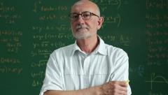 Older male teacher standing in front of a classroom chalkboard - stock footage