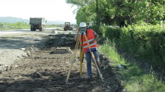 Land surveyor measuring the distance with modern equipment at road construction. Stock Footage