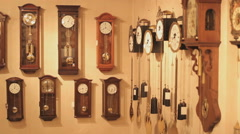 Antique wall clocks in a clock store, ticking the time, panshot - stock footage