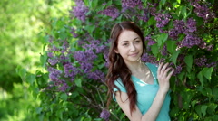 Young women walking outside in a park at the violet lilac tree Stock Footage