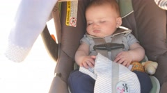 Newborn baby startled in his carseat Stock Footage