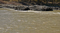 Close up view of rocky bank of Katun river during flood of muddy water Stock Footage