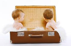 Twins sitting in a suitcase having fun, play, travel, family - concept - stock photo