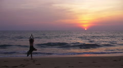 Nature Yoga - Young beautiful woman on beach at sunset - tree pose slow motion Stock Footage