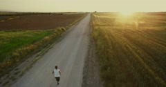 4K aerial footage of a runner at the fields at the sunset. Arkistovideo