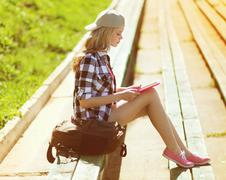 Girl with tablet pc working in the city park, student, education, modern yout - stock photo