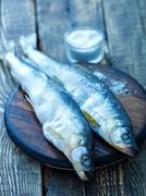 Raw fish with salt on wooden table Stock Photos