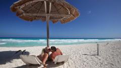 Couple relaxing on beach. Looking on each other and kissing. Caribbean honeymoon Stock Footage
