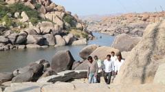 Men climbing up through large stones at the riverbank in Hampi. Stock Footage