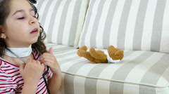 Little girl with sore throat examining her ill bear toy with a stethoscope Stock Footage