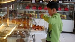 Asian child buying bread in shop - stock footage