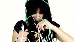 Cute young woman having trouble with cables and technology funny Stock Footage