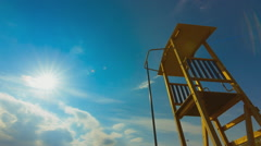 Summer timelapse, beach, lifeguard tower, sun, blue sky Stock Footage