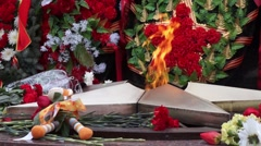 Eternal flame on victory day among flowers Stock Footage