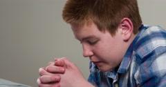 Boy saying prayer kneeling at bed 4k - stock footage