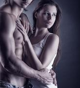 Young beautiful loving couple is embracing on a dark background - stock photo