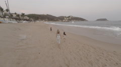 Family walking on the beach Stock Footage