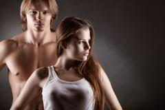 Young sexy girl with a guy on a dark background Stock Photos