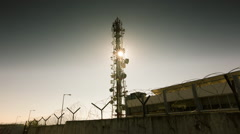 Sun rises behind big communication tower in energy facility barbed wire Stock Footage