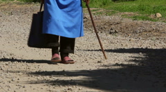 Old woman walking on a country road Stock Footage