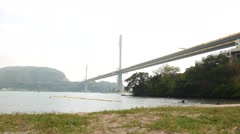 Ting Kau Bridge from the beach, daytime, Tsing Yi island on background Stock Footage