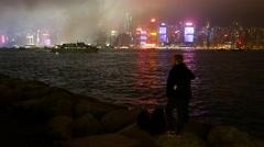Night Hong Kong shore, couple with camera watching beautiful cityscape Stock Footage