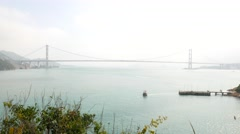 Little boat departs from wharf, Tsing Ma bridge on horizon, Ma Wan Channel view Stock Footage