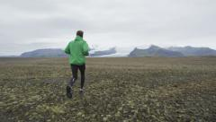 Man Jogging Towards Snowcapped Mountains - Athlete running Stock Footage