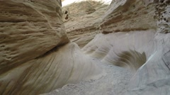 Tourists hike through a desert slot canyon in utah - stock footage