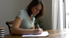 Young woman writing with pen in pad doing homeworks studying career coffee mug Stock Footage