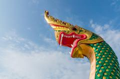 serpent king or king of naga statue in thai temple on blue sky background . - stock photo