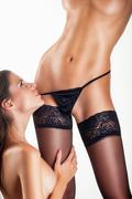 Two beautiful lesbian women in erotic foreplay game on a white background Stock Photos
