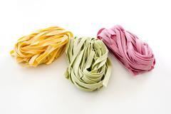 Bundles of dried ribbon color  pasta - stock photo