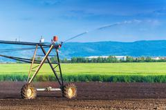 Stock Photo of Automated Farming Irrigation Sprinklers System in Operation