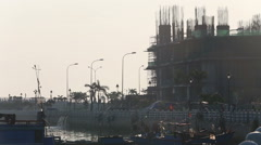 Fishing boats by city embankment against  building construction Stock Footage