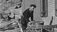Switzerland 1943: man preparing a table outside his mountain hut Stock Footage
