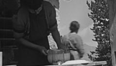 Switzerland 1943: woman cleaning pots in a mountain hut Stock Footage
